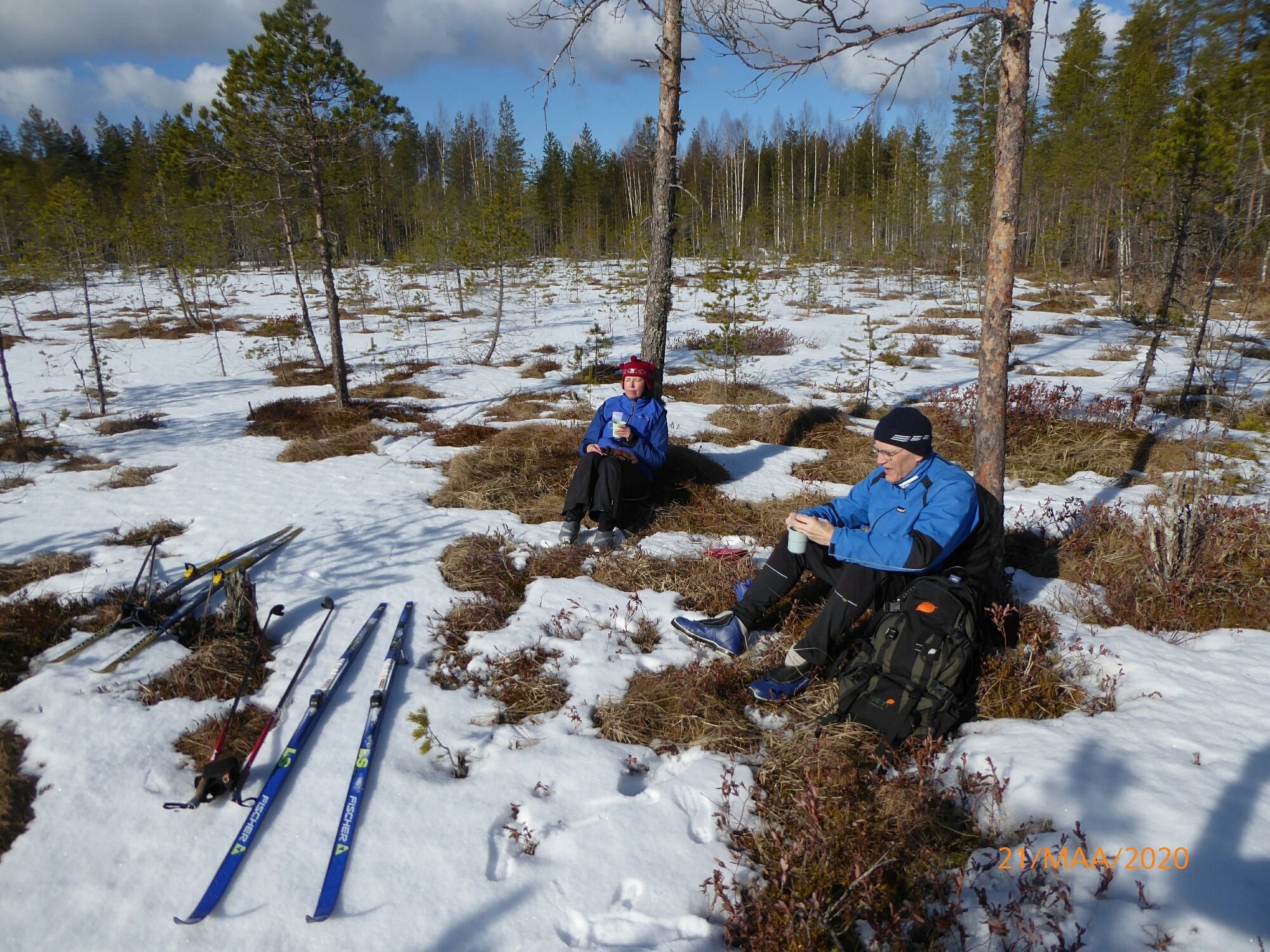 Kaksi hiihtäjää tauolla keväisessä luonnossa